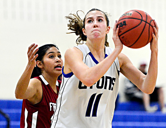 "Lyons' Olivia Raspotnik (11) goes up for a shot over Frontier Academy's Marlyn Granillo, left, during the game at Lyons High School on Thursday, Jan. 17, 2013. Frontier Academy beat Lyons 67-40. For more photos visit  <a href=""http://www.BoCoPreps.com"">http://www.BoCoPreps.com</a>. <br /> (Greg Lindstrom/Times-Call)"