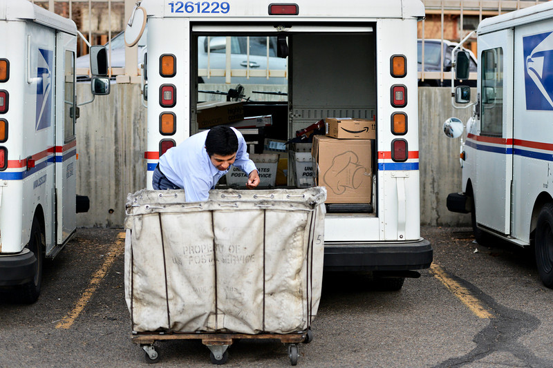 "Jose Chavez holds his left arm back as he loads his truck before leaving the Post Office at 201 Coffman St. in Longmont to deliver mail along his route on Tuesday, Dec. 18, 2012. Despite being diagnosed with multiple sclerosis in 2001, Chavez has been delivering mail along the same route for 12 years. The left side of his body is most affected by the ailment. For more photos and video visit  <a href=""http://www.TimesCall.com"">http://www.TimesCall.com</a>.<br /> (Greg Lindstrom/Times-Call)"