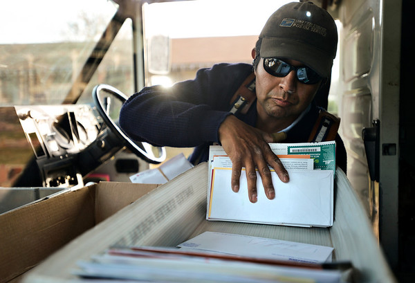 "Jose Chavez reaches for mail as he delivers along his route in Longmont on Thursday, Dec. 13, 2012. Despite being diagnosed with multiple sclerosis in 2001, Chavez has been delivering mail along the same route for 12 years. For more photos and video visit  <a href=""http://www.TimesCall.com"">http://www.TimesCall.com</a>.<br /> (Greg Lindstrom/Times-Call)"