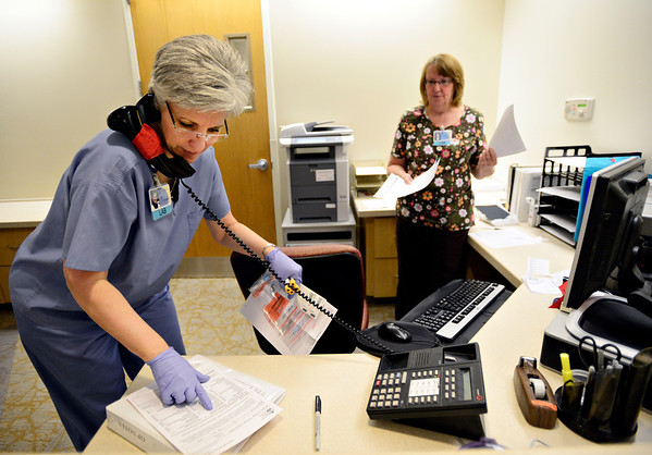 """Phlebotomist Deb Romero takes a call while medical assistant Colleen Divine, right, waits to hand her paperwork at the outpatient lab at Longmont United Hospital on Friday, Dec. 21, 2012. For more photos visit  <a href=""""http://www.TimesCall.com"""">http://www.TimesCall.com</a>.<br /> (Greg Lindstrom/Times-Call)"""