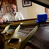 Piano Tuner Tom Carpenter watches his electronic tuning device as he works on customer Pat Lemmon's grand piano, Thursday, Dec. 6, 2012, at her home in Hygiene.<br /> (Matthew Jonas/Times-Call)