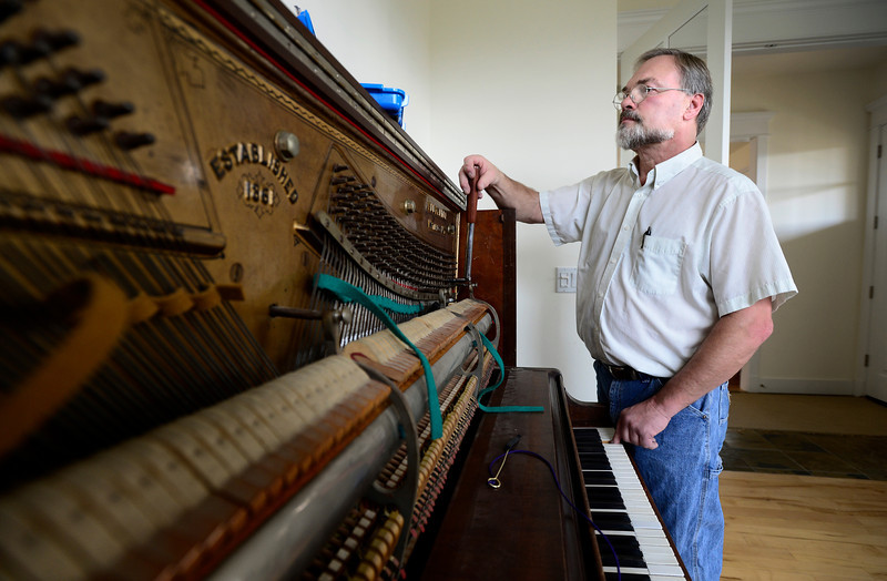 Piano Tuner Tom Carpenter uses a special wrench to turn the pins on the pin block while tuning an upright piano, Thursday, Dec. 6, 2012, at  customer Elisa Gray's house in Longmont. Carpenter tunes pianos throughout Longmont including many for the St. Vrain Valley School District.<br /> (Matthew Jonas/AP Photo/Longmont Times-Call)