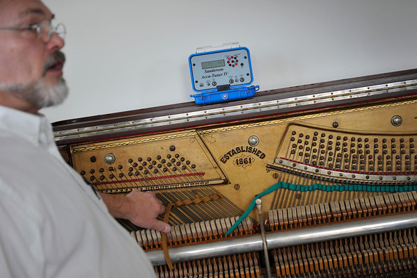 Piano Tuner Tom Carpenter uses an electronic Sanderson Accu-Tuner IV in combination with listening to the tone with his own ears to tune a piano, Thursday, Dec. 6, 2012, at customer Elisa Gray's house in Longmont.<br /> (Matthew Jonas/Times-Call)