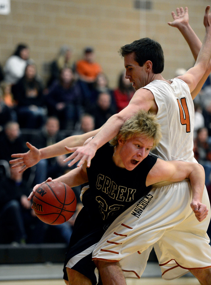 Silver Creek's Eric Machmuller drives underneath Mead's Ryan Lozinski in the second quarter Saturday night, Jan. 5, 2013 at Mead High School. (Lewis Geyer/Times-Call)