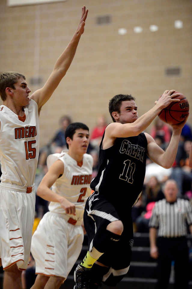 Silver Creek's Zane Lindsey drives to the basket past Mead's Griffin Nelson, left, and Aaron Cheung in the first quarter Saturday night, Jan. 5, 2013 at Mead High School. (Lewis Geyer/Times-Call)