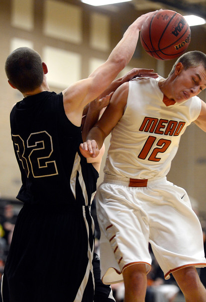 Mead's Cody Beaver and Silver Creek's Luke Goforth go after the ball in the second quarter Saturday night, Jan. 5, 2013 at Mead High School. (Lewis Geyer/Times-Call)