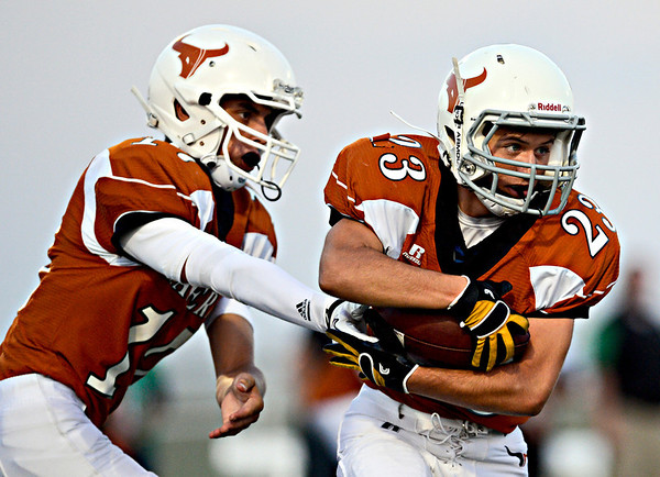 """Mead quarterback Griffin Nelson hands off to Logan Anderson (23) during the first half.  Mead faces St. Mary's during the varsity football game at Mead High School on Friday, Sept. 7, 2012.  For more photos visit  <a href=""""http://www.TimesCall.com"""">http://www.TimesCall.com</a>.<br /> (Greg Lindstrom/Times-Call)"""