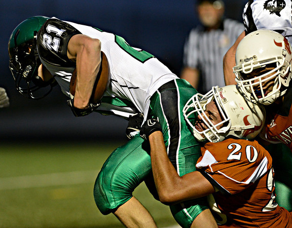 """Mead's Tate Aragon (20) brings down St. Mary's Ben Cipoletti (21) in the first half.  Mead faces St. Mary's during the varsity football game at Mead High School on Friday, Sept. 7, 2012.  For more photos visit  <a href=""""http://www.TimesCall.com"""">http://www.TimesCall.com</a>.<br /> (Greg Lindstrom/Times-Call)"""