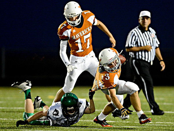 """Mead's Logan Anderson tries to keep his footing, but is brought down by St. Mary's Aidan Tiernan during the first half.  Mead faces St. Mary's during the varsity football game at Mead High School on Friday, Sept. 7, 2012.  For more photos visit  <a href=""""http://www.TimesCall.com"""">http://www.TimesCall.com</a>.<br /> (Greg Lindstrom/Times-Call)"""