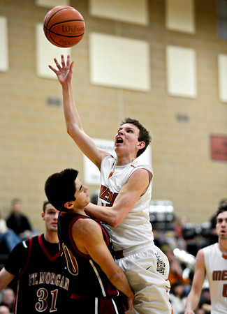 "Fort Morgan's Zach Garcia draws a charge from Mead's Conor Lamb, right, during the game at Mead High School on Wednesday, Feb. 27, 2013. Mead beat Fort Morgan 57-43 for its first-ever playoff victory. For more photos visit  <a href=""http://www.BoCoPreps.com"">http://www.BoCoPreps.com</a>.<br /> (Greg Lindstrom/Times-Call)"