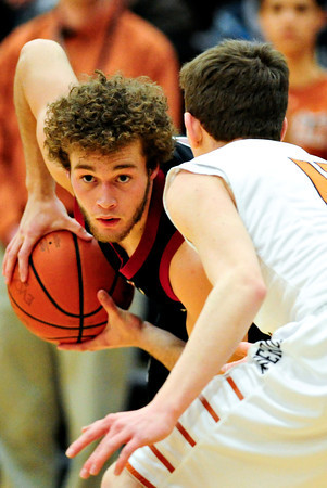 "Fort Morgan's Tony Zwetzig looks for an opening as Mead's Conor Lamb (11) defends during the game at Mead High School on Wednesday, Feb. 27, 2013. Mead beat Fort Morgan 57-43 for its first-ever playoff victory. For more photos visit  <a href=""http://www.BoCoPreps.com"">http://www.BoCoPreps.com</a>.<br /> (Greg Lindstrom/Times-Call)"