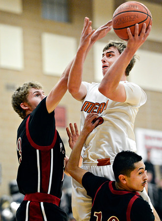 """Mead's Griffin Nelson goes up for a shot over Fort Morgan's Eric Kembel, left, and Leo Lopez (10) during the game at Mead High School on Wednesday, Feb. 27, 2013. Mead beat Fort Morgan 57-43 for its first-ever playoff victory. For more photos visit  <a href=""""http://www.BoCoPreps.com"""">http://www.BoCoPreps.com</a>.<br /> (Greg Lindstrom/Times-Call)"""