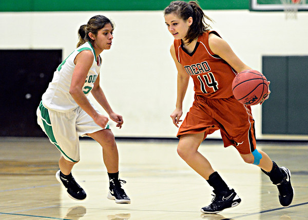 "Mead's Marina Hanlon (14) tries to drive past Niwot's Deyja Enriquez during the game at Niwot High School on Tuesday, Dec. 11, 2012. Mead beat Niwot 52-19. For more photos visit  <a href=""http://www.BoCoPreps.com"">http://www.BoCoPreps.com</a>.<br /> (Greg Lindstrom/Times-Call)"