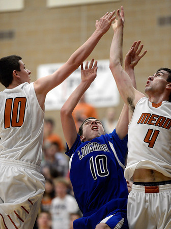 Longmont's Justinian Jessup gets caught between Mead's Walker Korell, left, and Ryan Lozinski Saturday night Jan. 26, 2013 at Mead High School. (Lewis Geyer/Times-Call)