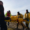"""A """"victim"""" is carried from the shore on a backboard during Mountain View Fire Rescue's annual ice rescue training Tuesday, Jan. 08, 2013 in a pond adjacent to the Weld County Services Center in Del Camino. Training will continue through Saturday for Mountain View's various shifts. (Lewis Geyer/Times-Call)"""