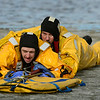 Firefighters Cody Bennett, left, and Gary Giles are pulled to shore during Mountain View Fire Rescue's annual ice rescue training Tuesday, Jan. 08, 2013 in a pond adjacent to the Weld County Services Center in Del Camino. Firefighters wore special suits to protect them from the 40 degree water tempratures. Training will continue through Saturday for Mountain View's various shifts. (Lewis Geyer/Times-Call)