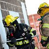 Randy Norris, left, and Ben Carter, firefighters with Mountain View Fire Rescue, work on a forced entry during a live fire drill Tuesday night, March 5, 2013, at the Boulder County Regional Fire Training Center in Longmont. Crews from Station 7, out of Dacono, and Station 3, out of Mead, practiced forced entry and transitional attacks during the drill.<br /> (Greg Lindstrom/Times-Call)
