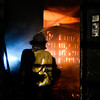 """Cody Bennett, Lt. in Training, keeps an eye on a fire on the second floor of a building at the Boulder County Regional Fire Training Center in Longmont as Mountain View Fire Rescue firefighters participate in a live fire drill Tuesday night, March 5, 2013. Crews from Station 7, out of Dacono, and Station 3, out of Mead, practiced forced entry and transitional attacks during the drill. """"We don't have that many fires. That's a good thing,"""" said Deputy Chief Steve Pischke. """"But when we do we need to be able to know how to react."""" <br /> (Greg Lindstrom/Times-Call)"""
