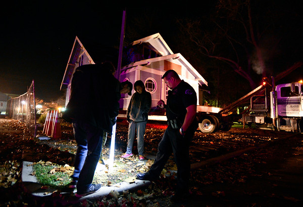 Workers remove a street sign in front of the blue house in Longmont on Wednesday, Nov. 14, 2012.<br /> (Greg Lindstrom/Times-Call)