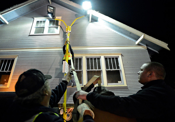 "Gary DeJohn Jr., center, tries to push a light pole away from the blue house while Mike Bucklen, left, and Heath Carroll attach a tow line in the parking lot of You Sell Auto as DeJohn Housemoving Inc., moves the blue house from 508 Terry St. to 1800 Kristy Court in Prospect on Wednesday, Nov. 14, 2012.  For more photos and a video visit  <a href=""http://www.TimesCall.com"">http://www.TimesCall.com</a>.<br /> (Greg Lindstrom/Times-Call)"
