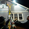 """Gary DeJohn Jr., center, tries to push a light pole away from the blue house while Mike Bucklen, left, and Heath Carroll attach a tow line in the parking lot of You Sell Auto as DeJohn Housemoving Inc., moves the blue house from 508 Terry St. to 1800 Kristy Court in Prospect on Wednesday, Nov. 14, 2012.  For more photos and a video visit  <a href=""""http://www.TimesCall.com"""">http://www.TimesCall.com</a>.<br /> (Greg Lindstrom/Times-Call)"""