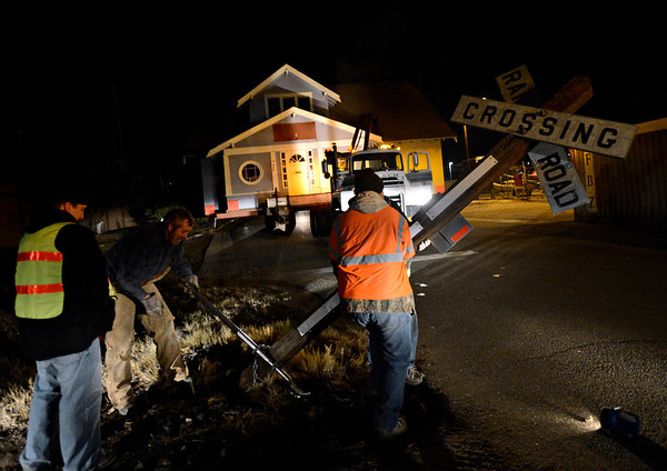"From left, Gary DeJohn Jr., Gary Sorensen, Mike Bucklen and Roger Merrill move a railroad crossing sign near the intersection of Coffman Street and First Avenue as DeJohn Housemoving Inc., moves the blue house from 508 Terry St. to 1800 Kristy Court in Prospect on Wednesday, Nov. 14, 2012.  For more photos and a video visit  <a href=""http://www.TimesCall.com"">http://www.TimesCall.com</a>.<br /> (Greg Lindstrom/Times-Call)"