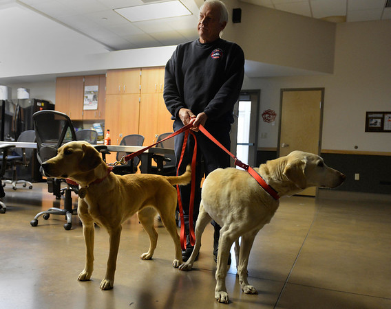 Bill Johnson, fire engine engineer, holds the leash of K-9s Holly, left, and Shadow, right, before an arson demonstration Monday, Nov. 26, 2012, at the Longmont Fire Department, Station 1. Holly replaced Shadow this past fall as the new arson sniffing dog. <br /> (Elaine Cromie/For the Times-Call)