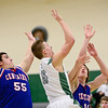 Niwot High School's Nate Merriman (No. 5) puts up a shot between Centaurus High School's Mike DeVries (No. 55) and Steven Jordan (No. 10), Friday, Feb. 15, at NHS. The Cougars defeated the Warriors, 56-53.<br /> (Matthew Jonas/Times-Call)