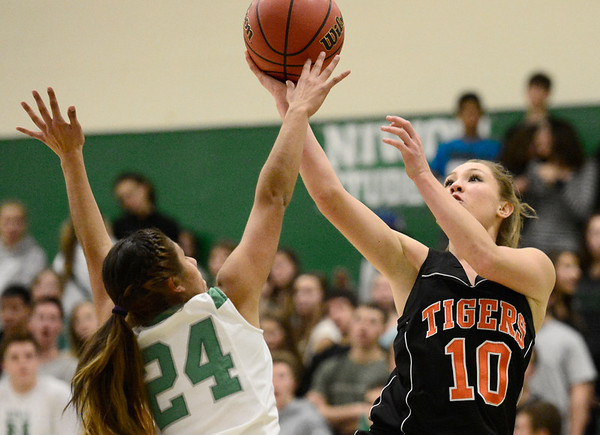 Erie High School's Amanda Ochoa (No. 10) puts up a shot over Niwot High School's Deyja Enriquez (No. 24) during the third quarter, Friday, Nov. 30, 2012, at NHS. The Tigers defeated the Cougars, 39-36.<br /> (Matthew Jonas/Times-Call)