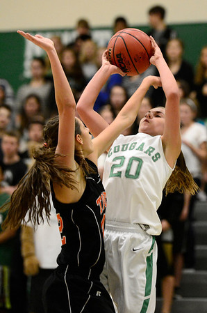 Niwot High School's Jaelyn Larson (No. 20) tries to put up a shot over Erie High School's Serena Gudino (No. 42) during the second quarter, Friday, Nov. 30, 2012, at NHS.<br /> (Matthew Jonas/Times-Call)