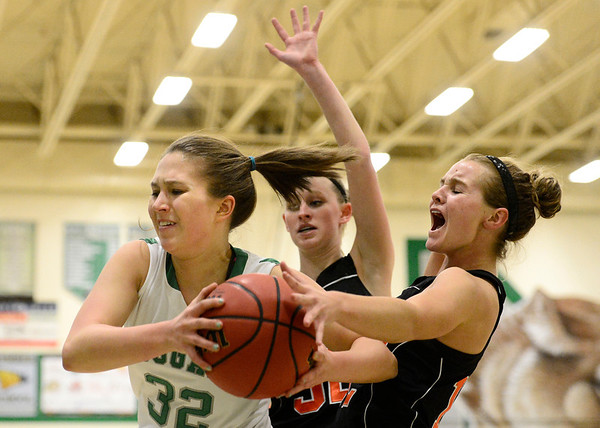 Niwot High School's Anna Dunnell (No. 32) tries to maintain control of the ball while pressured by Erie High School's Kenzie Kudrna (No. 12) and Haley Gallagher (No. 32) during the second quarter, Friday, Nov. 30, 2012, at NHS.<br /> (Matthew Jonas/Times-Call)