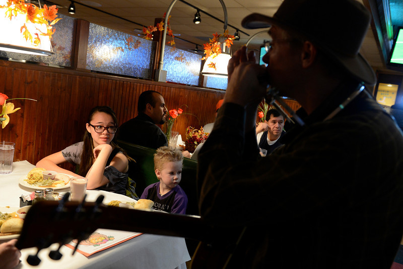 From left: Phoenix Zhang, 12, and Brigit Bard, 4, both of Longmont listen as Michael Bellmont plays the harmonica during the OUR Center's annual Thanksgiving Day dinner, Thursday, Nov. 22, 2012, at Old Chicago in Longmont.<br /> (Matthew Jonas/Times-Call)