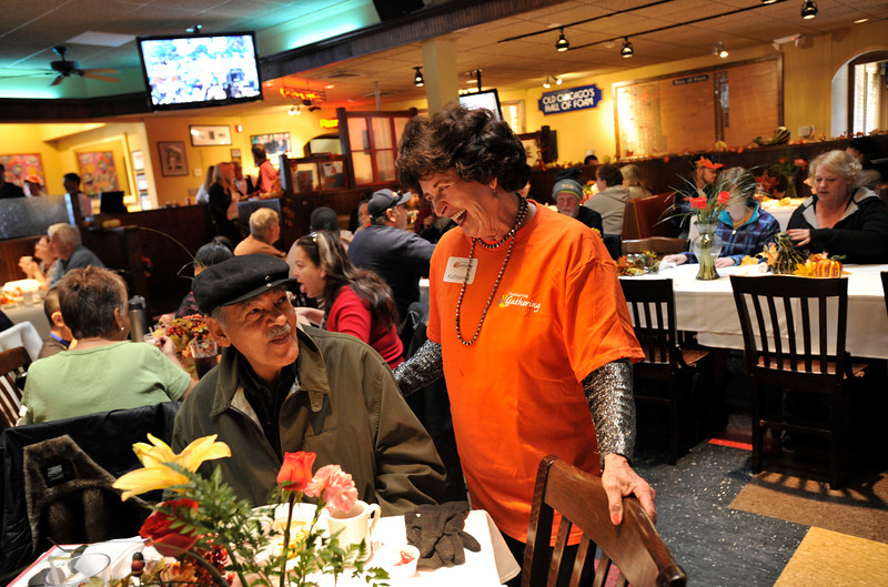 Volunteer Kathleen Bennett, of Estes Park, shares a laugh with David, no last name given, 76, of Longmont, during the OUR Center's annual Thanksgiving Day dinner, Thursday, Nov. 22, 2012, at Old Chicago in Longmont.<br /> (Matthew Jonas/Times-Call)