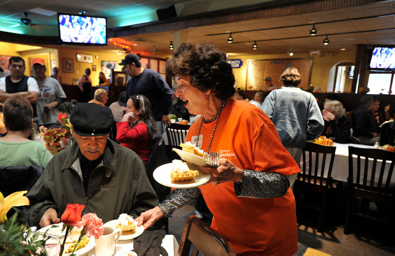 Volunteer Kathleen Bennett, of Estes Park, serves up slices of pumpkin pie to David, no last name given, 76, of Longmont, during the OUR Center's annual Thanksgiving Day dinner, Thursday, Nov. 22, 2012, at Old Chicago in Longmont.<br /> (Matthew Jonas/Times-Call)