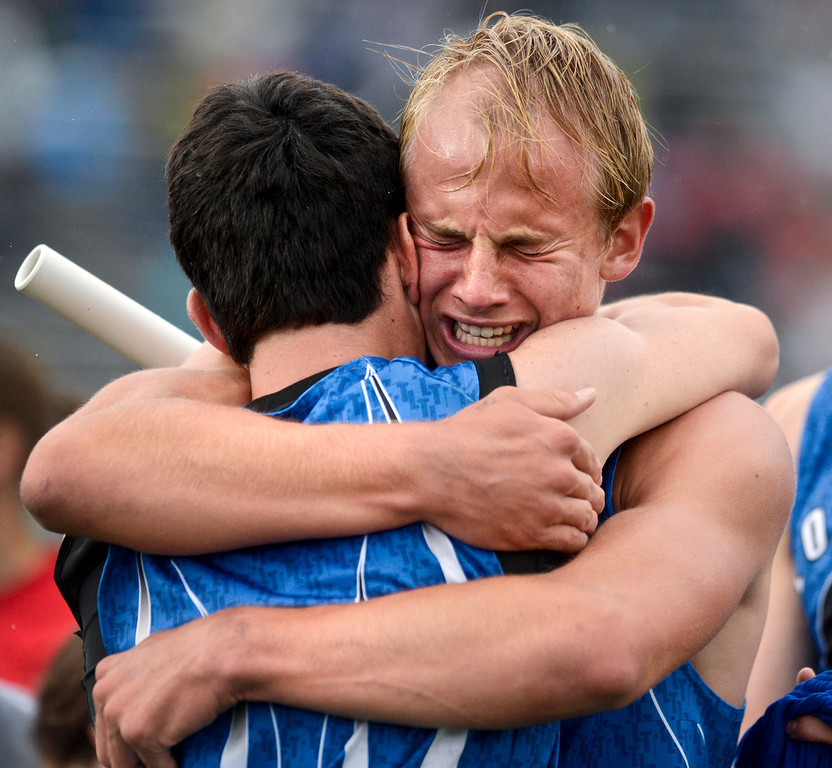 Longmont's Forrest Wetterstrom, right, celebrates with teammate Braden Hitchcock after the Trojan's third place finish in the 4A boys 4x400 meter relay during the last day of the 2012 Colorado High School State Track and Field Championships at Jefferson County Stadium on Saturday, May 19, 2012.<br /> <br /> (Greg Lindstrom/Times-Call)