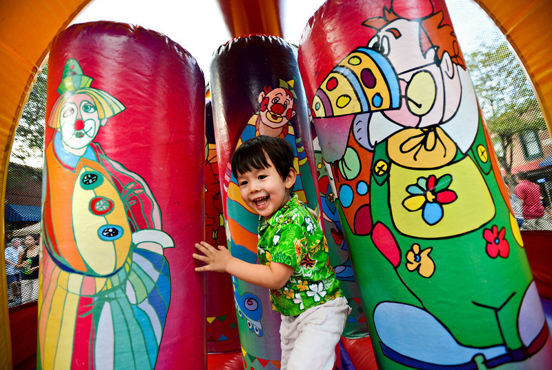 Chaze Yeap, 3, of Longmont, laughs as he exits an inflatable obstacle course at the Festival on Main in downtown Longmont on Friday, August 24, 2012.