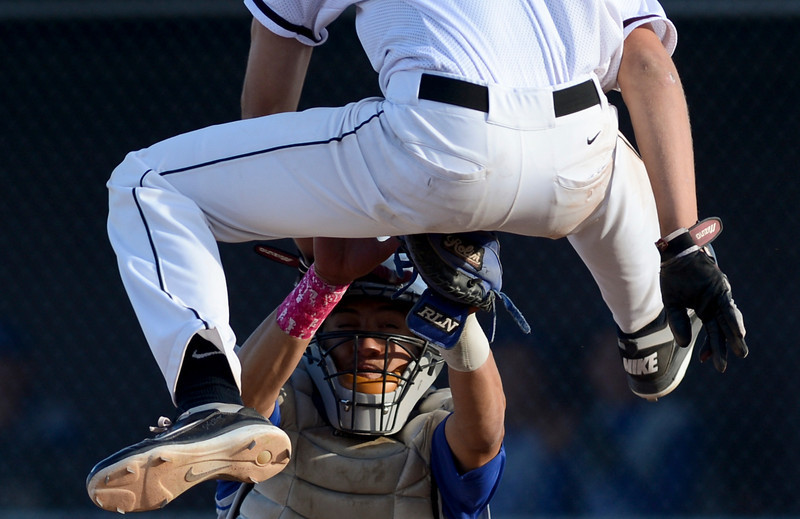 Silver Creek's Greg Reynolds is tagged out while trying to jump over Longmont catcher Julian Moroyoqui in the fifth inning.  Longmont beat Silver Creek 8-5 during the varsity baseball game at Silver Creek High School on Thursday, April 5, 2012.<br /> (Greg Lindstrom/Times-Call)