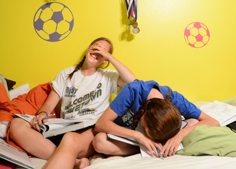 Aubree Adams, left, and her twin sister Kaylee laugh after messing up one of their secret handshakes while working on homework in their Longmont home on Wednesday, April 25, 2012.  <br /> (Greg Lindstrom/Times-Call)