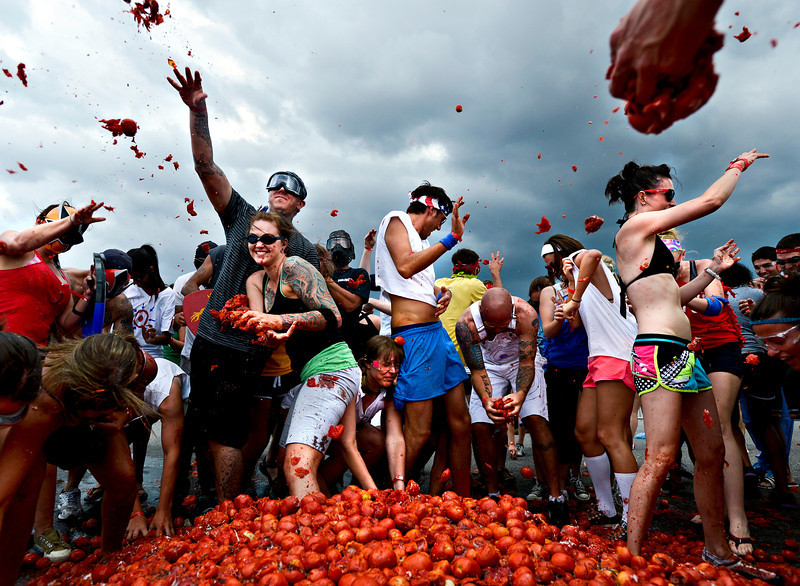 "Thousands of participants throw overly-ripe tomatoes at the start of the Tomato Battle at Dick's Sporting Goods Park in Commerce City on July 7, 2012.  The tomatoes used were past-ripe and not for human consumption.  The afternoon event featured live music, a costume contest and a beer garden- in addition to the food fight.  For more photos visit  <a href=""http://www.timescallmedia.com"">http://www.timescallmedia.com</a>.<br /> (Greg Lindstrom/Times-Call)"
