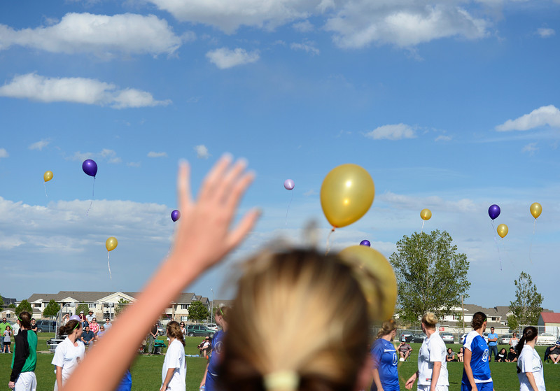 Silver Creek's Macey Colburn waves to balloons being released by members of the Longmont and Silver Creek soccer teams during halftime.  The balloons commemorate Delaney Goodner, who passed away on December 9, 2011.  Goodner was a Silver Creek junior at the time.  Longmont and Silver Creek tied 1-1 during the varsity soccer game at Silver Creek High School on Tuesday, May 1, 2012.<br /> (Greg Lindstrom/Times-Call)