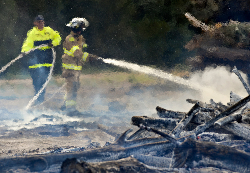 "Distorted by heat from a pile of wood burning near Golden Ponds, Longmont Firefighters work to extinguish a fire on Thursday August 30, 2012.  According to Dan Higgins, assistant fire chief for the Longmont Fire Department, flames were 10-15 feet high when crews arrived Thursday afternoon.  ""It had potential,"" Higgins said.  There was a permit for a burn in the area earlier in the week, according to officials, but there was a Red Flag Warning Thursday and no burning was allowed.  The cause of the fire is still under investigation."