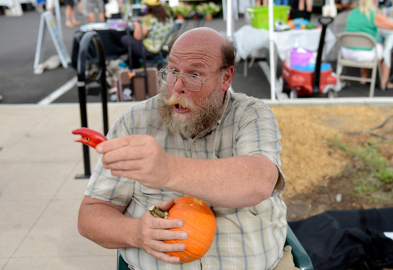 Patrick King, executive chef of Boulder's Outlook Hotel, shows an onlooker the dinosaur head he made from a pepper during a fruit and vegetable carving demonstration at the downtown Longmont Farmer's Market Thursday Sept. 06, 2012. (Lewis Geyer/Times-Call)