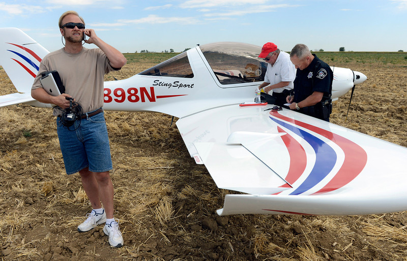 Pilot Brian Garrett, left, of Westminster, talks on his cell phone Saturday Sept. 01, 2012 after making an emergency landing in a wheat stubble field at 14880 Weld County Road 5. Garrett was taking his private pilot exam with FAA pilot examiner Drew Chitiea, center, when the single engine plane suffered a prop failure. Talking with Chitiea is Boulder County Sheriff's deputy Stuart Holt. No one was injured. (Lewis Geyer/Times-Call)