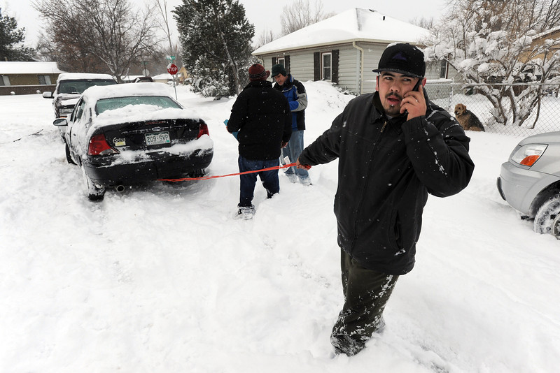 Miguel Gonzalez makes a phone call while trying to get his car unstuck on Aspen Street, near 10th Avenue, during a snowstorm Friday Feb. 03, 2012. (Lewis Geyer/Times-Call)