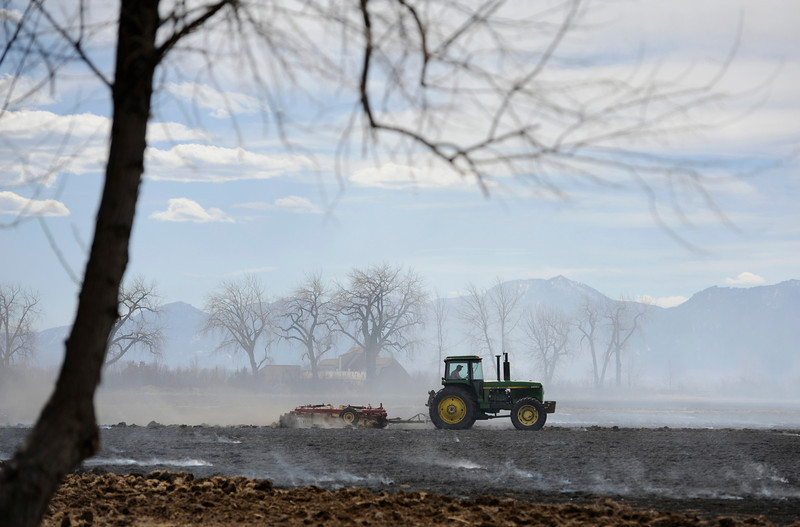 Smoke fills the air as a tractor plows a field after an agricultural controlled burn Friday, March 16, 2012 near the intersection of Alpenglow Court and County Road 73 in Niwot. Large plumes of smoke have been seen throughout the Longmont from controlled burns.<br /> (Matthew Jonas/Times-Call)