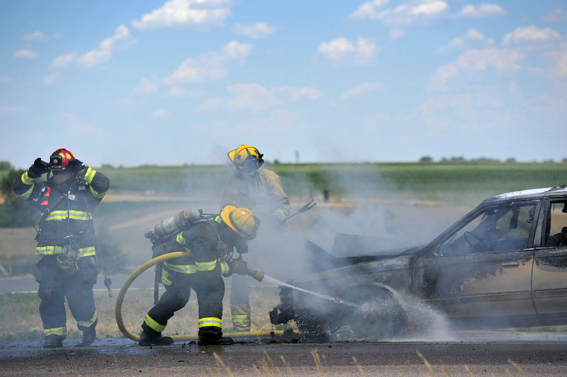 Mountain View Fire Rescue firefighters work to extinguish a car fire, Thursday, July 19, 2012, north of Weld County Road 34 on Northbound Interstate 25. One lane of the highway was closed in the northbound direction and traffic in both directions moved slowly as emergency personnel worked the scene.<br /> (Matthew Jonas/Times-Call)