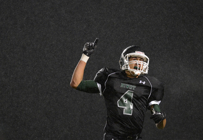 Niwot High School's Forrest Lee (No. 4) celebrates as the rain falls during the third quarter, Friday, Oct. 5, 2012, at Everly-Montgomery Field in Longmont. The Mountain Lions defeated the Cougars, 49-22.<br /> (Matthew Jonas/Times-Call)