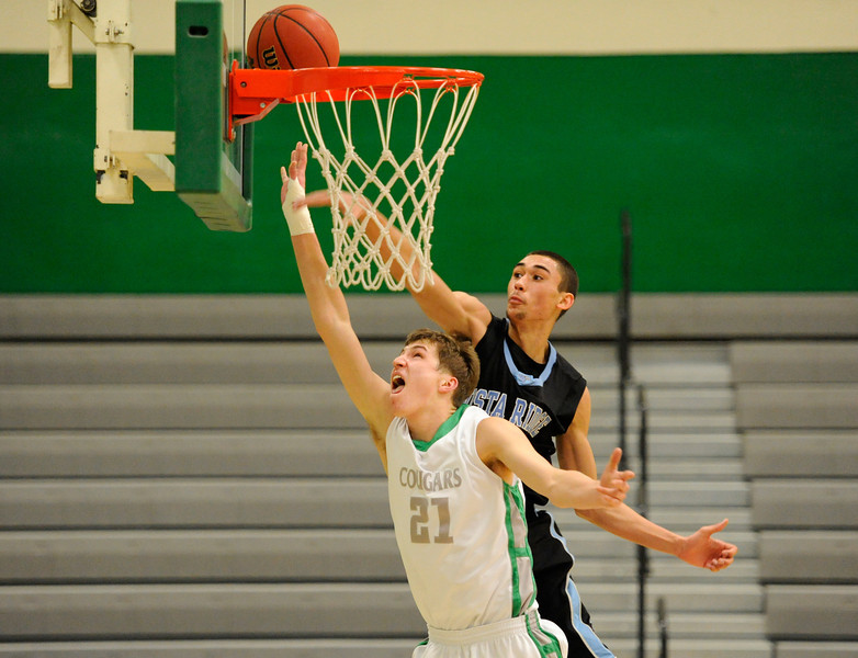 Niwot High School's Cody Heimann (No. 21) puts in a basket past Vista Ridge High School's Josh McKenzie (No. 32) during the second quarter Tuesday, Feb. 21, 2012 at NHS. The Cougars defeated the Wolves, 71-60, to advance to the next round of playoffs.<br /> (Matthew Jonas/Times-Call)
