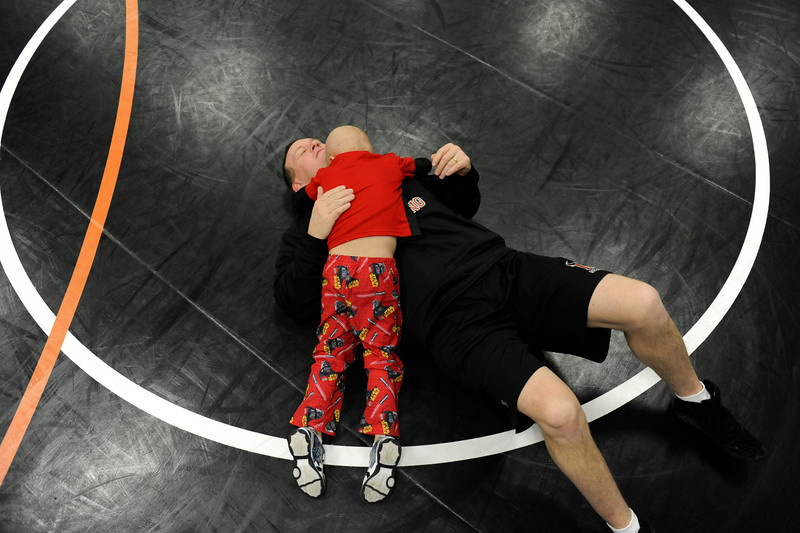 """Trey Tatham, 4 years old, wrestles with his father, Mead High School wrestling coach Ty Tatham, at varsity wrestling practice Wednesday, Feb. 8, 2012 at Mead High School. Trey Tatham has Rhabdomyosarcoma, a soft tissue cancer. On Thursday, Feb. 9, at 2:30pm, more than 30 students, faculty and volunteers will have their heads shaved at a """"Trims for Trey"""" assembly.<br /> (Matthew Jonas/Times-Call)"""