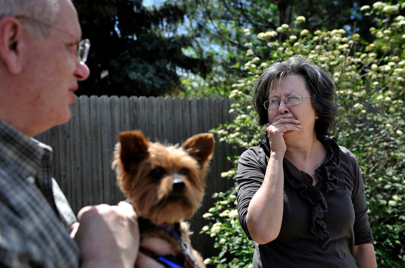 Alda Crill, right, fights to hold back her emotions while standing on the spot where her dog Belagrin was attacked by a pit bull as her husband Rikk Crill, holding Zoar, a 10 year old Yorkie, looks on Thursday, April 26, 2012 in their neighborhood.<br /> (Matthew Jonas/Times-Call)